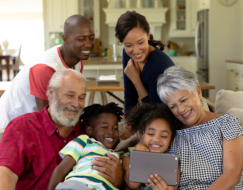 Family gathers together to watch videos transfered to digital on a tablet.