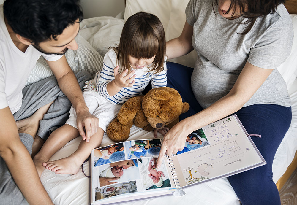 Parents with young daughter select items for digital transfer